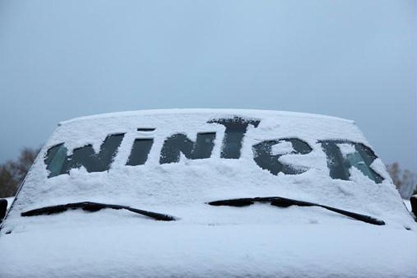 """przód samochodu z napisem """"winter"""" na zaśnieżonej szybie"""
