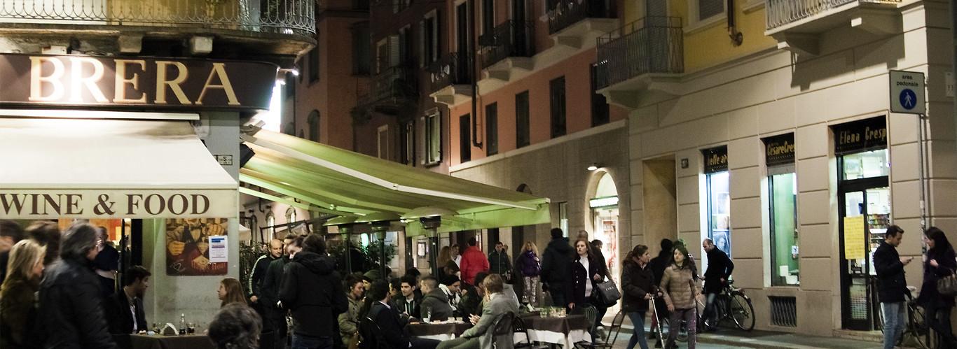 mediolan - widok na gwarną ulicę z kafejkami nocą