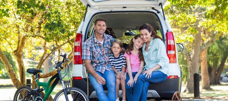 zdjęcie szczęśliwej rodziny siedzącej w bagażniku busa
